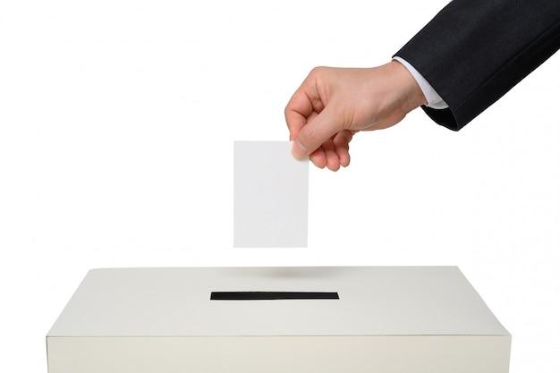 La mano del hombre baja la boleta en la urna.