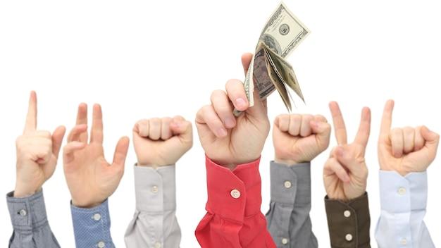 La mano del hombre con billetes de un dólar en el espacio de otras manos levantadas. negocios y finanzas. ganador del concurso.