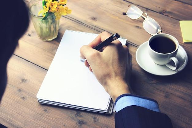 Mano de hombre en el bloc de notas, café, bolígrafo y vasos en la mesa