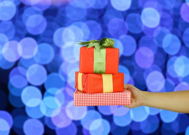 Mano del hombre con una caja de regalo de navidad roja sobre fondo azul bokeh.