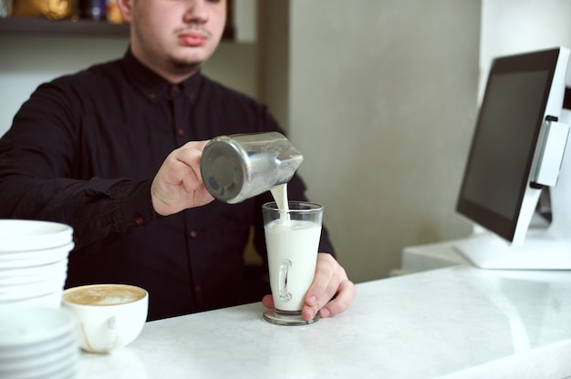 Mano de hombre en camisa negra haciendo café con leche o capuchino vertiendo leche haciendo arte latte
