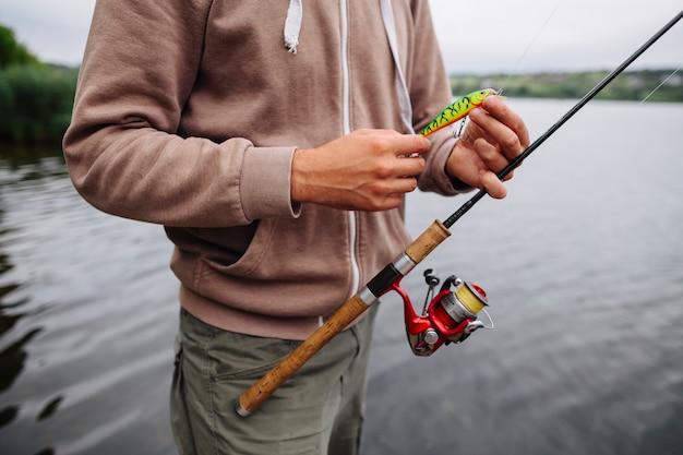 La mano del hombre con cebo y barra de pesca
