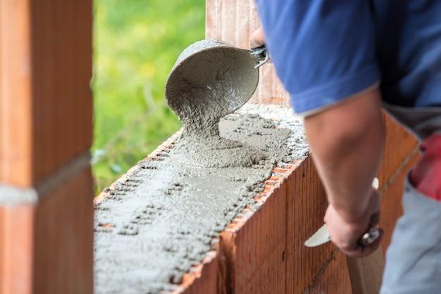Mano de hombre construyendo muro de ladrillos