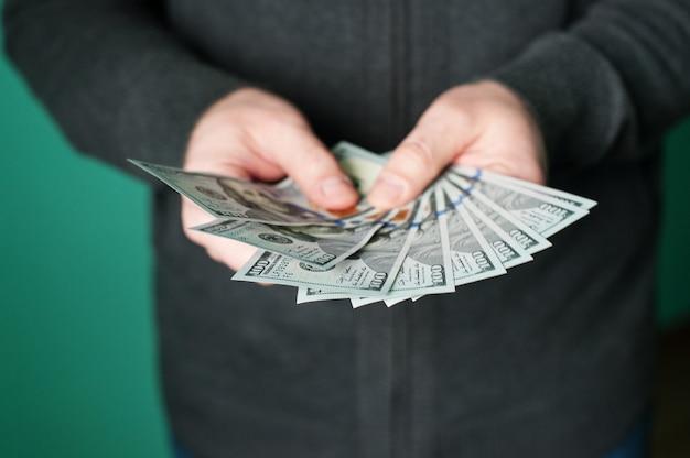 Mano del hombre dando billetes de 100 dólares