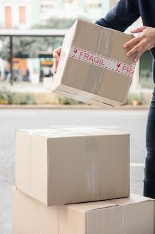 Mano del hombre de entrega que lleva el paquete