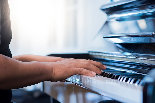 La mano del hombre es tocar el piano en la mañana.