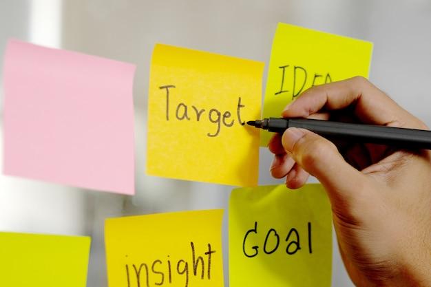 Mano de hombre escribir palabra objetivo en nota adhesiva en la oficina