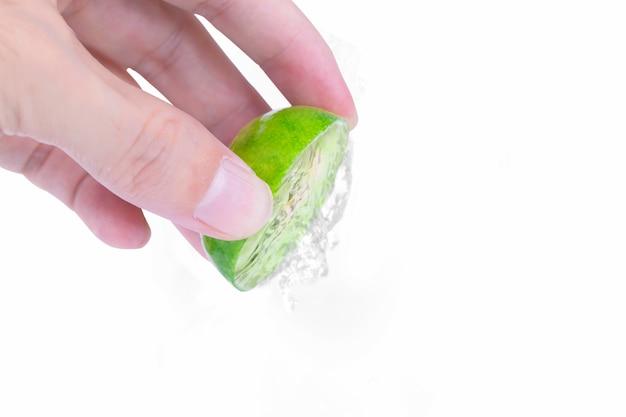 La mano de un hombre exprime el jugo de una rodaja de limón verde medio con gota de limón aislado en blanco