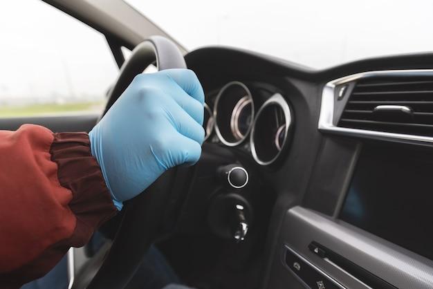 La mano de un hombre en un guante protector en el volante en el habitáculo.