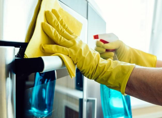 La mano del hombre en el guante con un trapo de limpieza