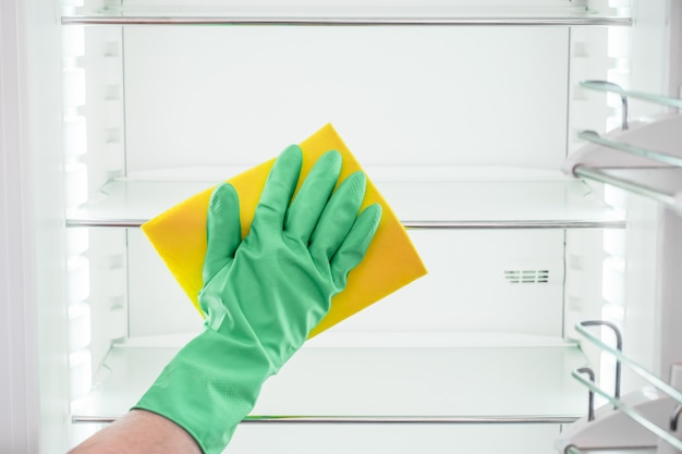 La mano del hombre en el guante verde que limpia el refrigerador vacío