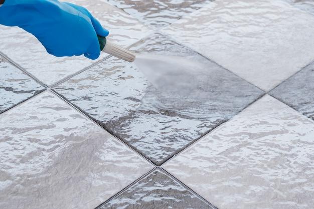 Mano del hombre con guantes de goma azul con una manguera para limpiar el piso de baldosas.