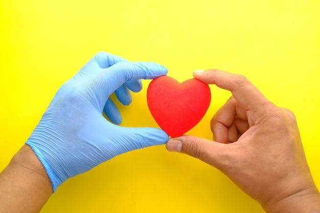 La mano del hombre en guantes protectores con corazón rojo sobre amarillo