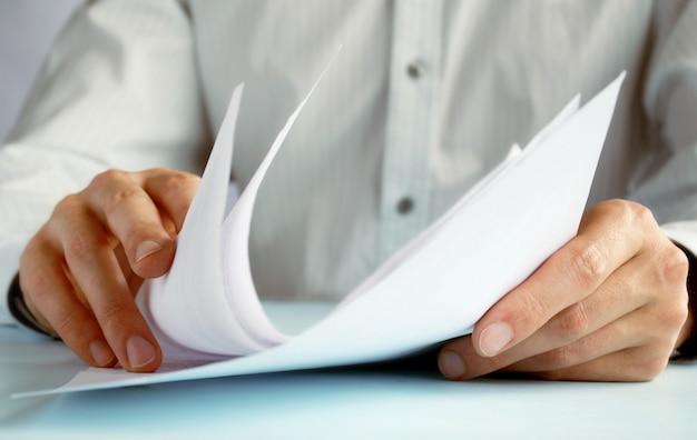 La mano del hombre hace anotaciones en documentos oficiales.