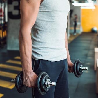La mano del hombre haciendo ejercicio con pesas