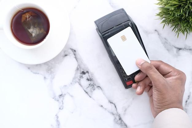 La mano del hombre haciendo pagos sin contacto con tarjeta de crédito en la mesa frontal