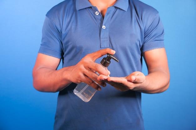 Mano de hombre joven con gel desinfectante en espacio azul.