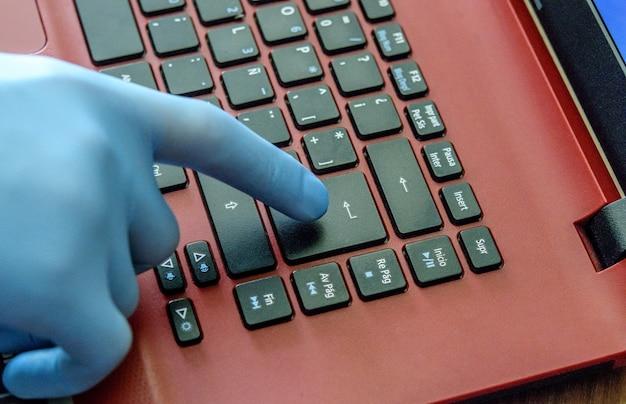 Mano de hombre joven en guantes médicos en la tecla del ordenador portátil.