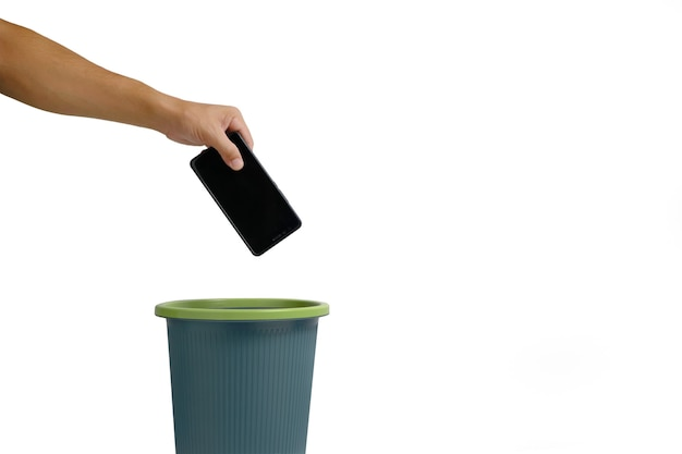 La mano del hombre lanza el teléfono celular a la papelera sobre fondo blanco.