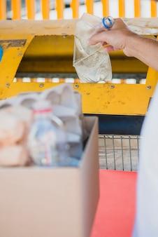 Mano del hombre lanzando botella de plástico en papelera de reciclaje