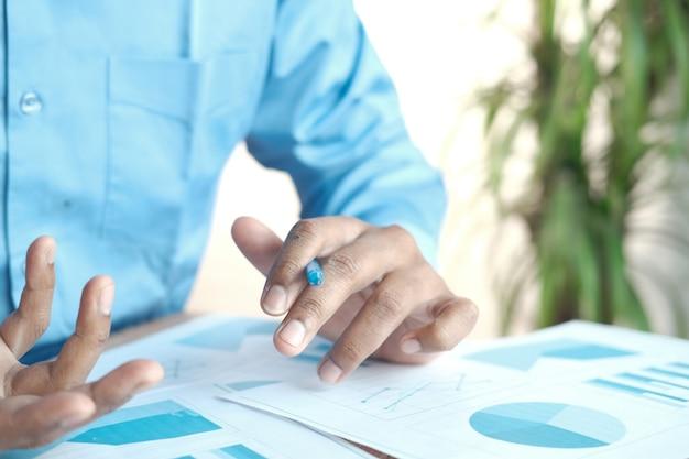 Mano de hombre con lápiz analizando gráfico de barras en papel