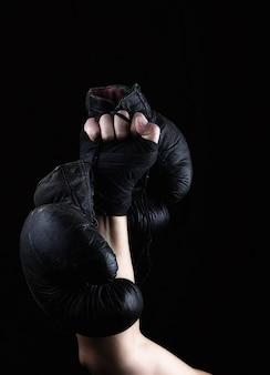 La mano del hombre levantada sostiene un par de viejos guantes de boxeo de cuero negro