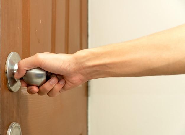 La mano del hombre llegando al pomo de la puerta abriendo la puerta de color marrón.