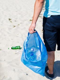 La mano del hombre llevando una bolsa de basura azul de plástico de desecho en la arena