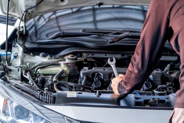 La mano del hombre mecánico sostiene la herramienta de la llave inglesa, el servicio de inspección y el servicio de automóviles