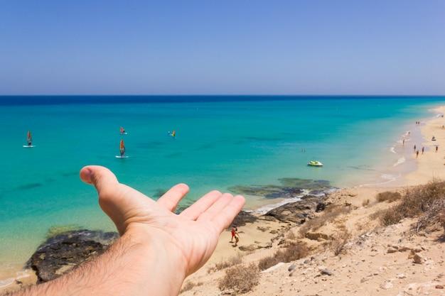 Mano de hombre mostrando a la gente practicar windsurf en aguas turquesas en fuerteventura españa