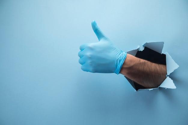 La mano del hombre mostrando el pulgar hacia arriba en guantes en escena azul