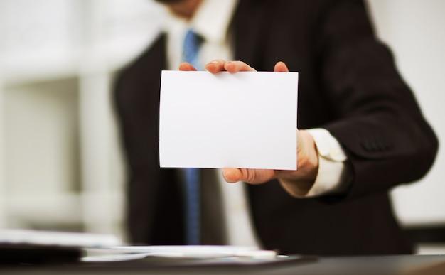 Mano de hombre mostrando la tarjeta de visita