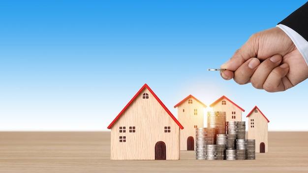 Mano de hombre de negocios apilamiento de monedas de crecimiento creciente con modelo de casa en un escritorio de madera con fondo azul.