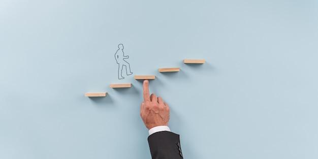 Mano de un hombre de negocios apoyando un escalón de madera para que un hombre silueta caminen hacia arriba