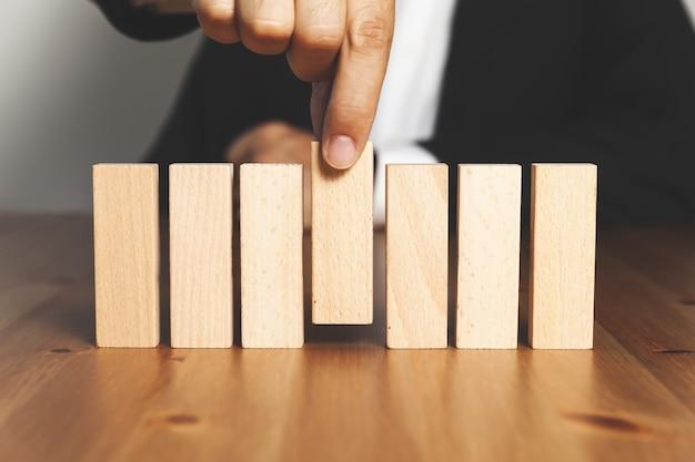 Mano de hombre de negocios arreglando o recogiendo un bloque de madera - concepto de éxito empresarial
