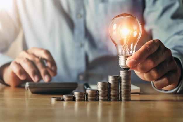 Mano de hombre de negocios con bombilla. concepto de idea con innovación e inspiración. idea de contabilidad financiera