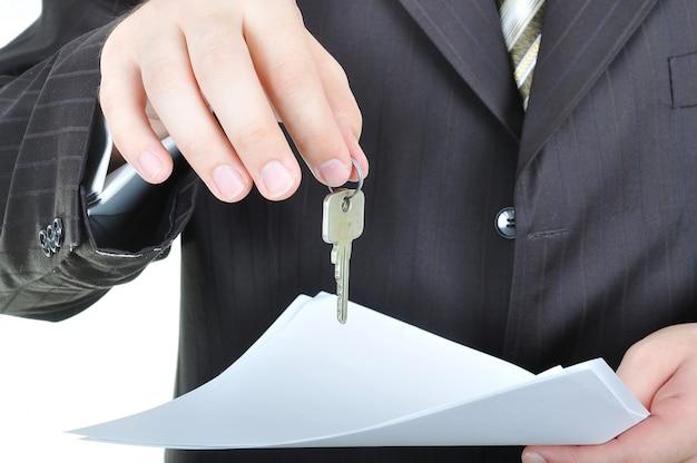 Una mano de hombre de negocios y la clave, acuerdo de papel