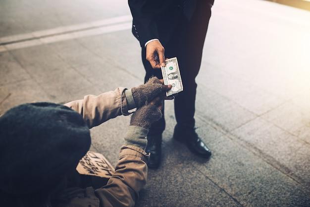Mano de hombre de negocios dando dólar a mendigo sin hogar en el puente.