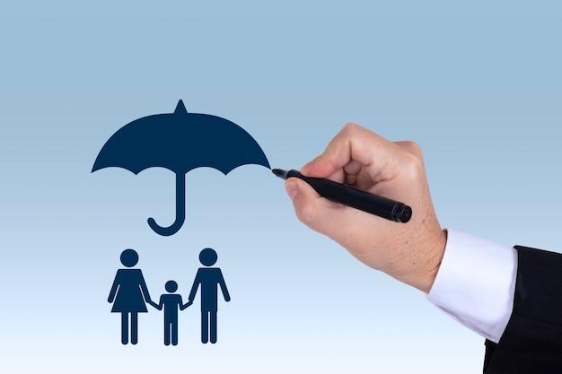 Mano de hombre de negocios dibujando un paraguas sobre un concepto de familia para protección, seguridad, finanzas y seguros. foto de alta calidad