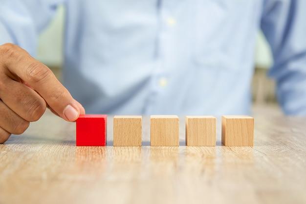 La mano del hombre de negocios elige el blog de madera rojo sin gráfico.