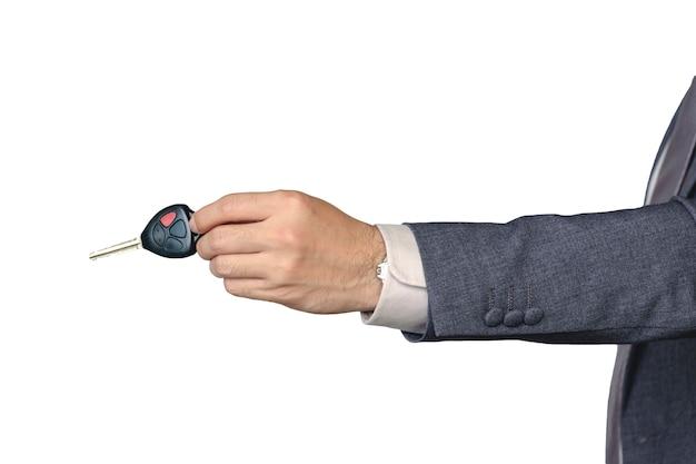 La mano de un hombre de negocios está enviando una llave del coche en su mano sobre un fondo blanco aislado.