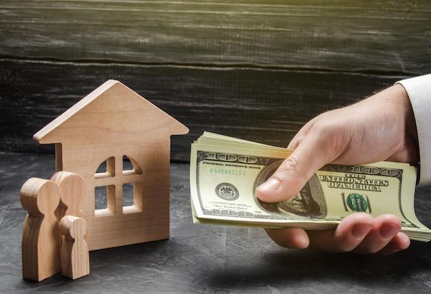La mano de un hombre de negocios extiende un fajo de dinero a las figuras de la familia cerca de la casa de madera.