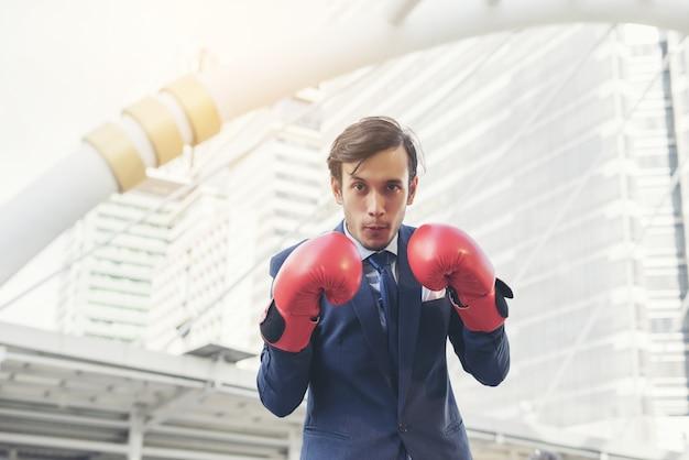 Mano de hombre de negocios con guantes de boxeo.
