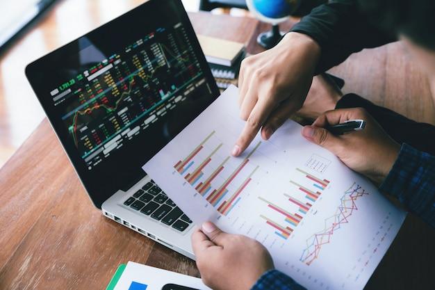 Mano de hombre de negocios joven con pluma y gráfico gráfico señalando discutiendo con colegas sobre marketing y progreso empresarial.
