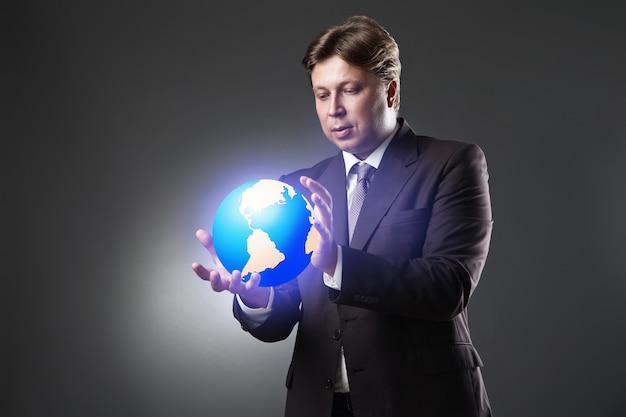 Mano del hombre de negocios mantenga el globo terráqueo en la oscuridad
