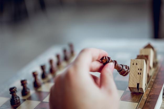 Mano de hombre de negocios moviendo ajedrez a modelos de construcción y casa en juego de ajedrez, competencia