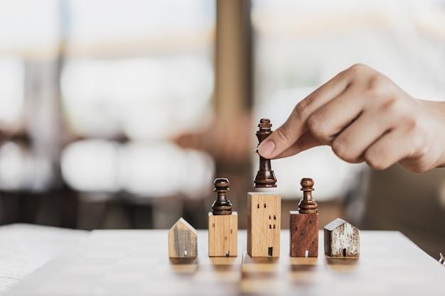 Mano de hombre de negocios moviendo ajedrez a modelos de construcción y casa en juego de ajedrez