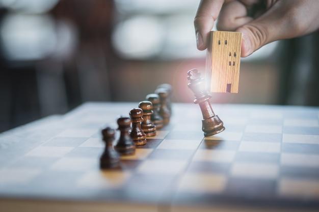 Mano de hombre de negocios en movimiento construcción y modelos de casas en juego de ajedrez.