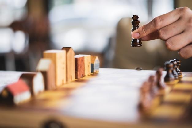 Mano de hombre de negocios en movimiento edificio y modelos de casas en juego de ajedrez, éxito de competencia.
