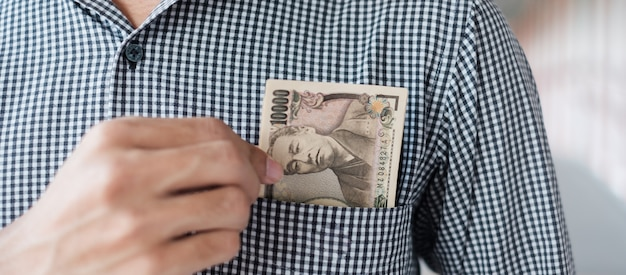 Mano de hombre de negocios con pila de billetes de yen japonés. conceptos de negocios, dinero, inversión, finanzas y pagos